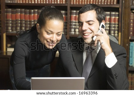 Businessman and woman in office smiling while looking at laptop and talking on phone. - stock photo