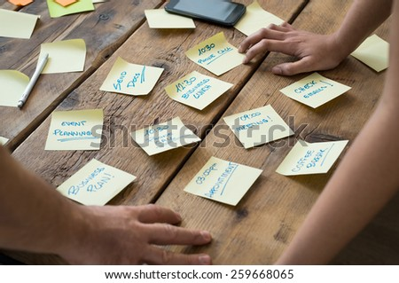 Businessman and woman leaning on desk with various sticky note papers  - stock photo