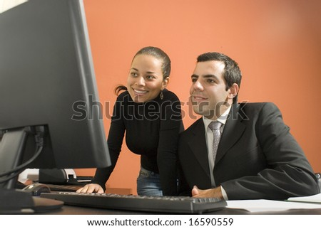 Businessman and woman look at a computer together. Horizontally framed photo. - stock photo