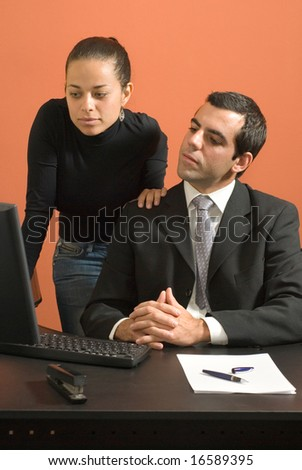 Businessman and woman look at a computer together. They both look serious. Vertically framed photo. - stock photo