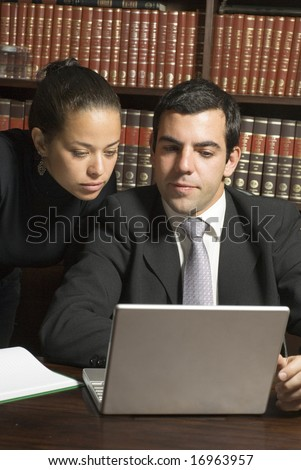 Businessman and woman looking at a laptop computer with bookshelves in the background.  Vertically framed photo. - stock photo