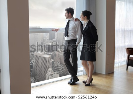 Businessman and woman looking out of a window - stock photo