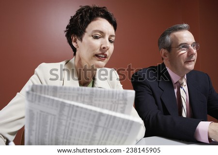 Businessman and Woman Reading Newspaper - stock photo