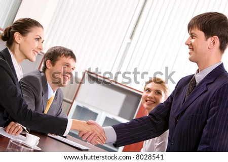 Businessman and woman shaking hands at meeting in the office - stock photo