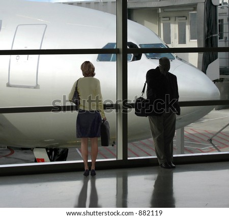 Businessman and woman wait for their flight - stock photo