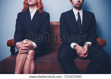 Businessman and woman waiting on sofa in lobby - stock photo