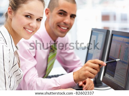Businessman and woman working on computers - stock photo