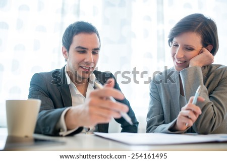 Businessman and woman working together in the office sitting at a desk discussing paperwork in front of a bright window. - stock photo