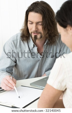 Businessman and women having a meeting, man showing plans or writing notes on paper. Selective focus placed on man.