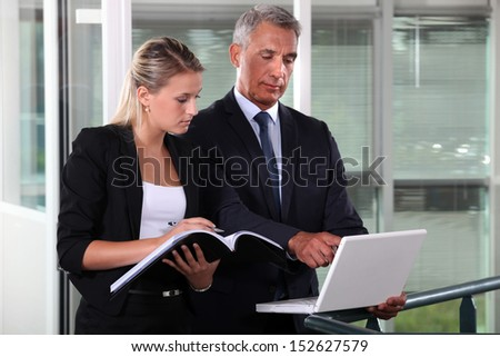 Businessman and young assistant rushing to prepare presentation - stock photo
