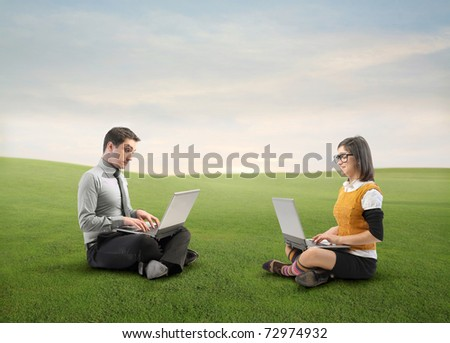 Businessman and young woman using laptops on a green meadow - stock photo