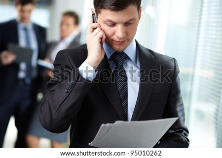 Businessman answering a call while his colleagues having a discussion in the background - stock photo
