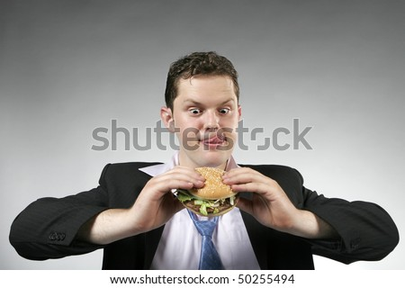 Businessman anxious to eat his lunch. Studio shot