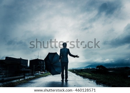 businessman are holding an umbrella, dark image