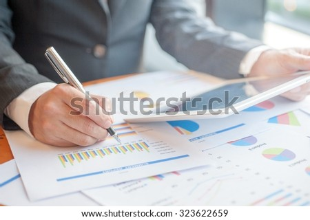 Businessman are recorded statistics. use smartphone ,Business finance, tax, accounting, statistics and analytic research concept - stock photo