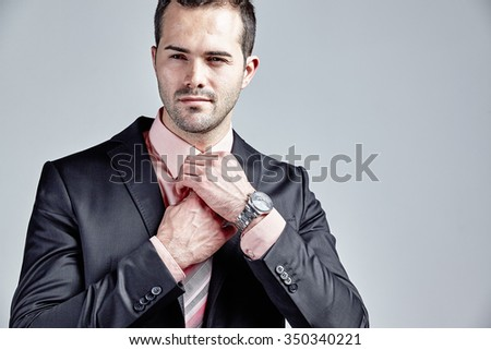 Businessman arranging his tie isolated over grey - stock photo