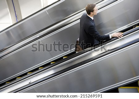 Businessman ascending escalator, side view, elevated view