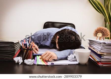 Businessman asleep at office desk with finance sheet calculator and coffee.(concept for overworked) (Dark vintage tone) - stock photo
