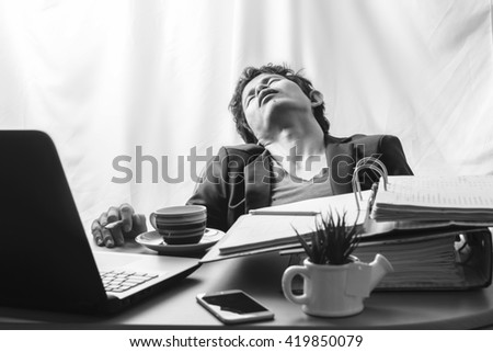 Businessman asleep at office desk with finance sheet calculator and coffee.concept for overworked (gloomy tone) - stock photo