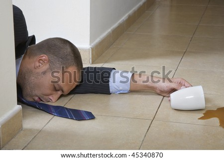 Businessman asleep in the office with spilt coffee - stock photo