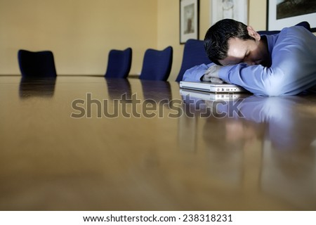 Businessman Asleep on Conference Table - stock photo
