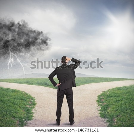 Businessman at a crossroads with storm and sunshine - stock photo