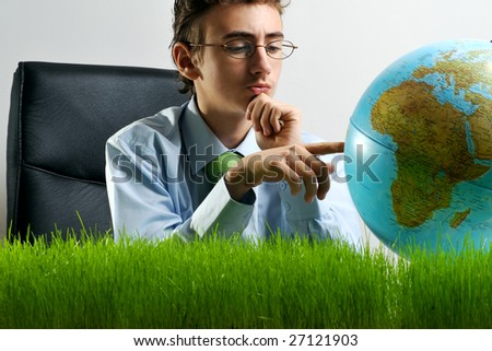 Businessman at a desk with grass pointing on Earth globe - stock photo