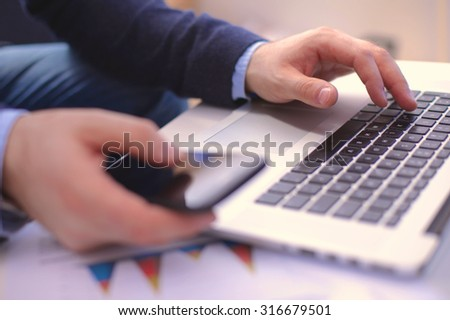 Businessman at a table with a smartphone and a laptop - stock photo