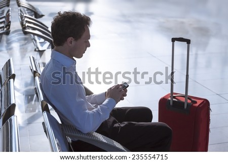 Businessman at airport with smartphone and suitcase checking emails before boarding - stock photo