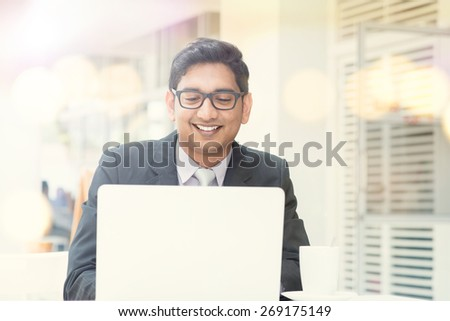 Businessman at cafeteria, having a cup of coffee and using internet. - stock photo