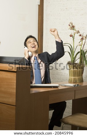 Businessman at desk holding a phone and his arm in the air in celebration. He is laughing. Vertically framed photo.