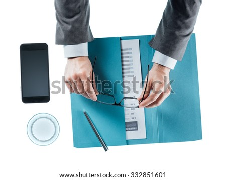Businessman at desk holding glasses on white background, hands close up top view