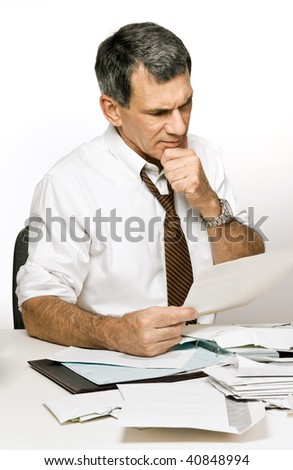 Businessman at desk in shirt and tie, reading a bill and looking worried and confused. - stock photo