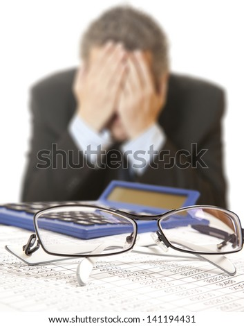 Businessman at desk in suit holding his head - stock photo