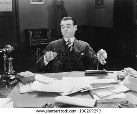 Businessman at desk looking at watch - stock photo