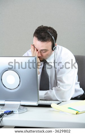 Businessman at desk with face in hand - stock photo