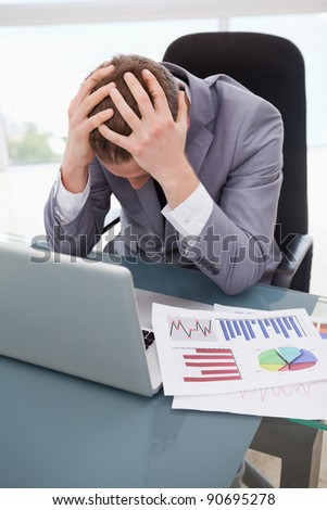 Businessman at his desk frustrated by statistics - stock photo