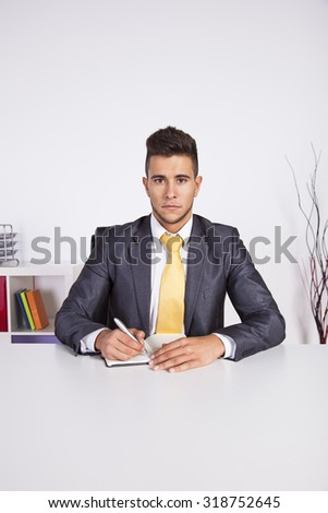 Businessman at his office taking some notes in his agenda