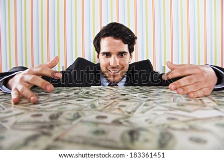 Businessman at his office with lots of money - stock photo