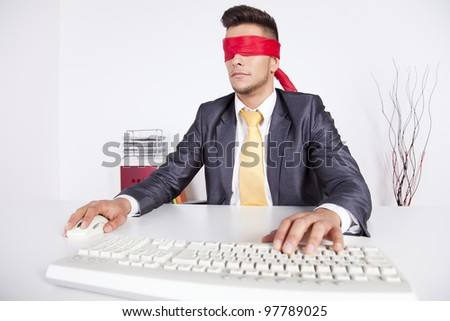 Businessman at his office with scarf covering his eyes while working with his computer - stock photo