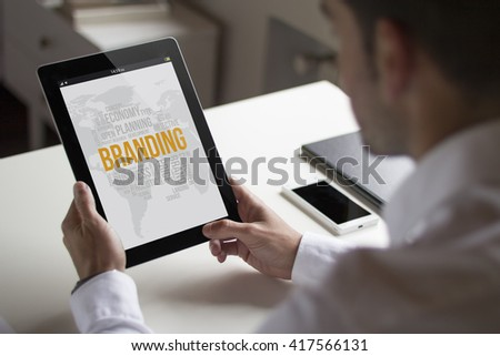 businessman at office holding a tablet showing branding. All screen graphics are made up. - stock photo