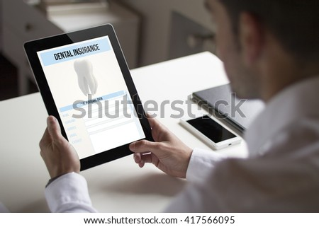 businessman at office holding a tablet showing dental insurance. All screen graphics are made up.
