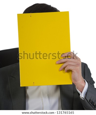 businessman at office sits in a chair having closed a face of yellow color the folder for documents