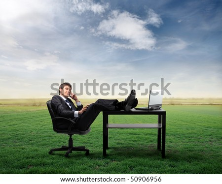 Businessman at telephone sitting at a desk on a green meadow - stock photo