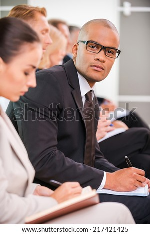 Businessman at the conference. Side view of business people sitting in a row and writing something in their note pads while confident African man in eyewear looking at camera  - stock photo