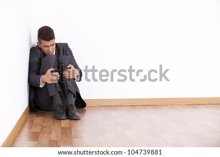 Businessman at the corner of his office room with fear - stock photo