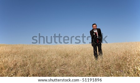 businessman at the field shouting at the megaphone to you