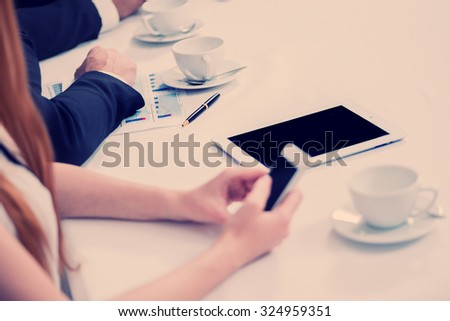 Businessman at the meeting calling on the phone. Four smiling successful businessmen sitting at table in office while discussing their of business doings. Young people talking in office - stock photo
