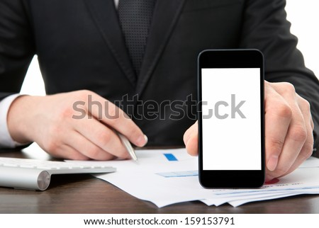 businessman at the office holding a touch phone with isolated screen  - stock photo