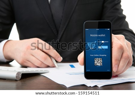 businessman at the office holding a touch phone with mobile wallet onlain shopping on the screen - stock photo